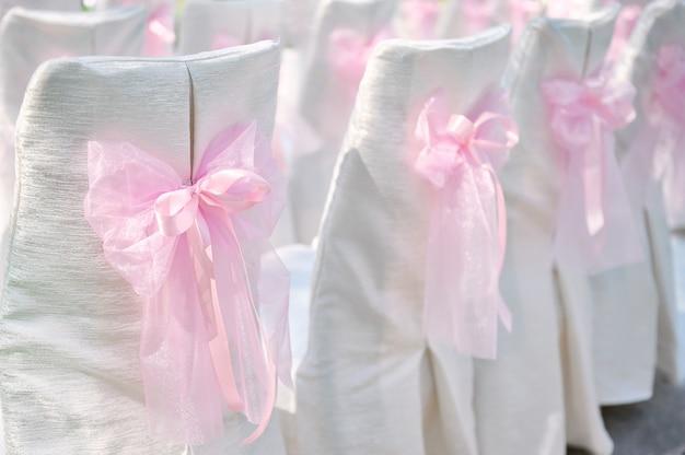 Dekoracja na ślubnych krzesłach różowi łęk