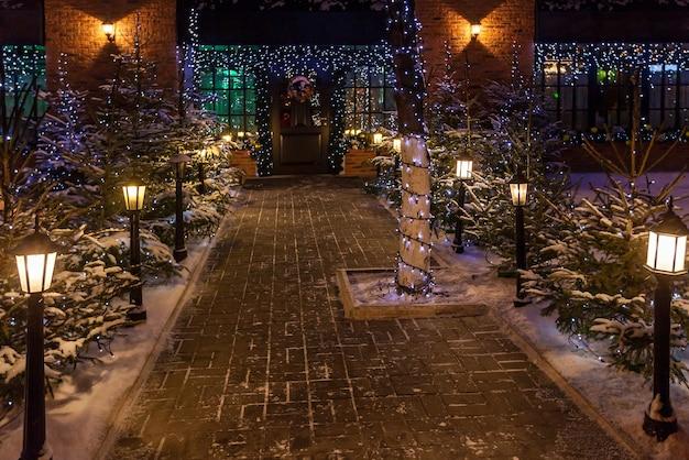Dekoracja noworoczna. nowy rok tło na zewnątrz, wgląd nocy choinki, światła, girlandy i altana ze śniegiem na ziemi.