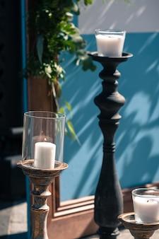 Dekoracja ślubna na zewnątrz, niebieski drewniany ekran, białe świece
