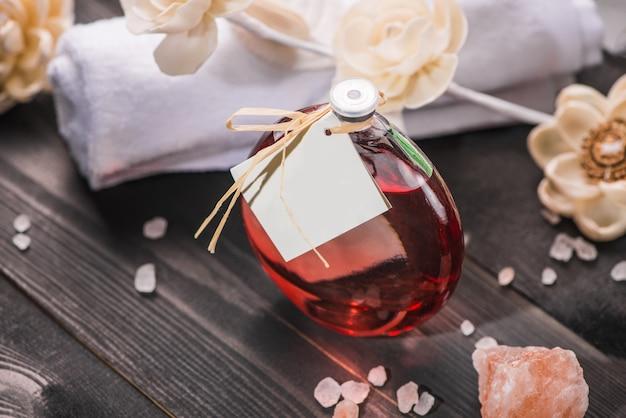 Dekoracja spa. butelka olejku eterycznego i suszonych kwiatów.