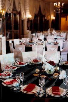 Dekoracja stołów z płonącymi świecami, wystrój w odcieniach czerni, czerwieni i bieli