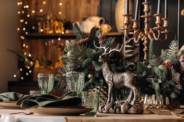 Dekoracja stołu świątecznego, stół bankietowy ze szklankami przed podaniem jedzenia, zbliżenie świątecznego stołu obiadowego z sezonowymi dekoracjami, kryształowymi kieliszkami i ozdobnym jeleniem