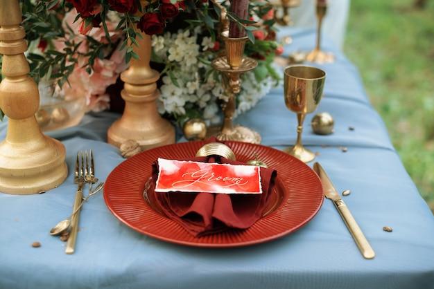 Dekoracja stołu weselnego w kolorach złotym i czerwonym.