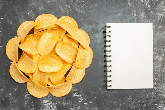 Dekoracja stołu z domowych chipsów ziemniaczanych na notebooku na szarym tle