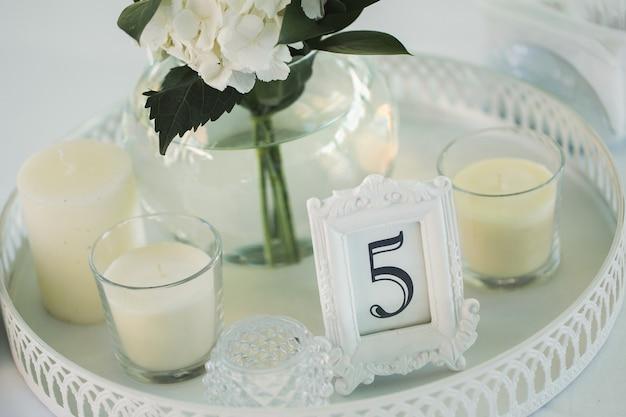 Dekoracja stołu z numerami kwiatów i świecami