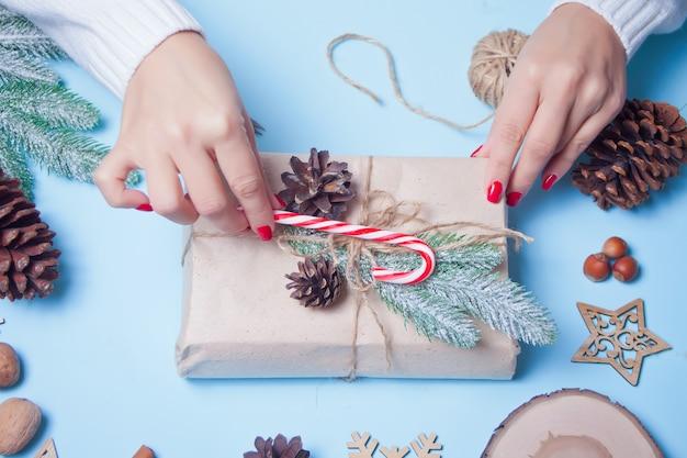 Dekoracja świąteczna. ręcznie robiony wystrój. kobieta owijania pudełko. widok z góry