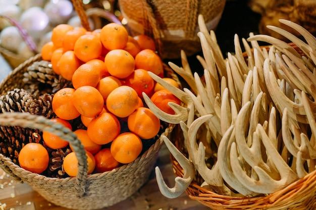 Dekoracja świąteczna w koszach mandarynki szyszki i ozdoby na choinkę