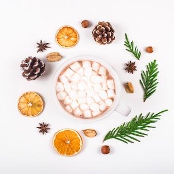 Dekoracja świąteczna zero odpadów na boże narodzenie, ułożona w okrągłej ramce z filiżanką kakao pośrodku.