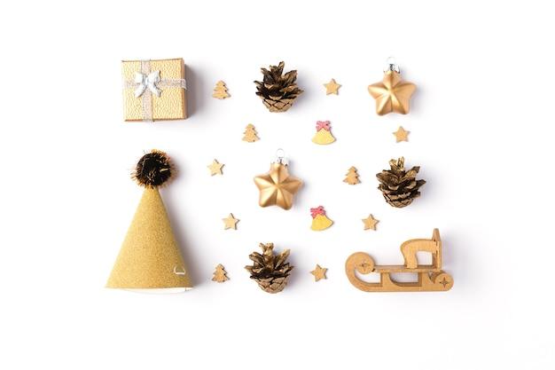 Dekoracja świąteczna. złoty prezent, złote ozdoby świąteczne z gwiazdami i saniami, szyszki sosnowe na białym tle. płaski układanie, widok z góry
