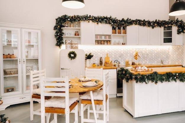 Dekoracja świątecznego stołu w kuchni, stół bankietowy ze szklankami przed podaniem jedzenia, zbliżenie świątecznego stołu obiadowego z sezonowymi dekoracjami, kryształowymi kieliszkami i ozdobnym jeleniem