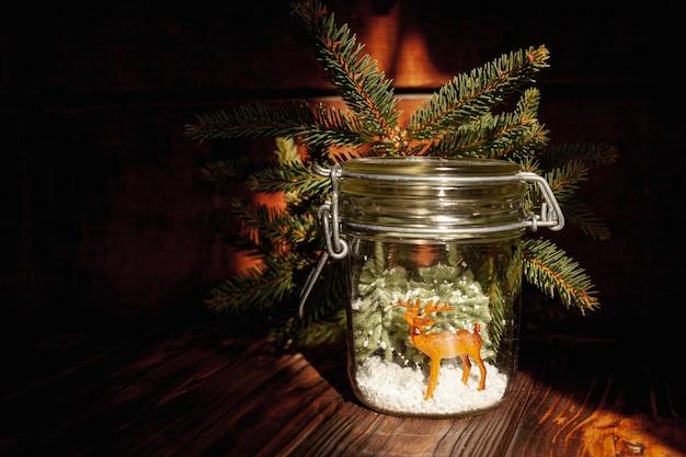 Dekoracja świątecznym słoikiem z gałęziami i jeleniem
