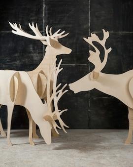 Dekoracja sylwestrowa i bożonarodzeniowa jelonek ze sklejki i drewna na ciemnym tle