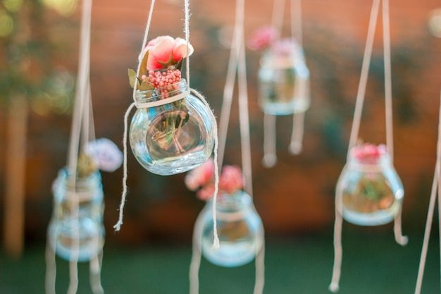 Dekoracja szklany słoik z kwiatami wiszące z rozmyciem tła ogrodu. nieostrość