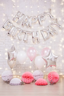 Dekoracja urodzinowa - balony z życzeniami urodzinowymi, gwiazdki i papierowe kulki nad białą ceglaną ścianą ze światłami