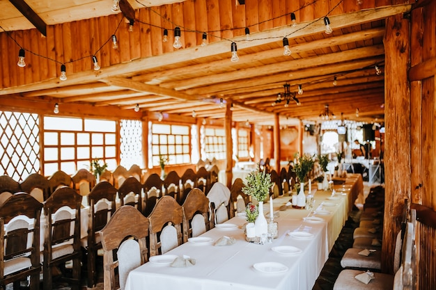 Dekoracja weselna. miejsce dla gości udekorowane kwiatami i roślinami na przyjęciu