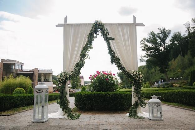 Dekoracja weselna na świeżym powietrzu. kwiatowy wystrój w pięknym białym łuku. piękny widok na drzewa.
