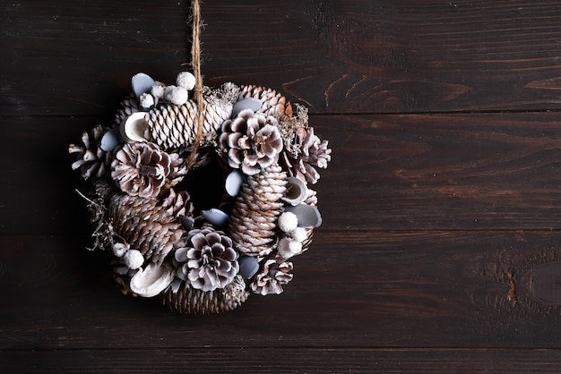 Dekoracja wieniec na białe drzwi wykonane z sosny i jodły na ciemnym drewnianym, copyspace