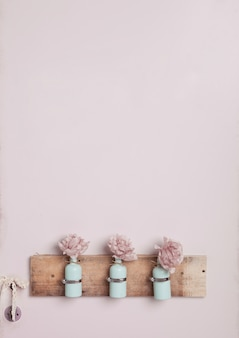 Dekoracja wnętrz z butelkami na różowej ścianie
