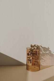Dekoracja wnętrza: gałązka eukaliptusa w wazonie z brązowego szkła z cieniami słonecznymi na ścianie