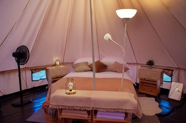 Dekoracja wnętrza namiotu w nowoczesnym glampingu. podwójne łóżko i inne meble w namiocie. ekoturystyka i cywilizacja