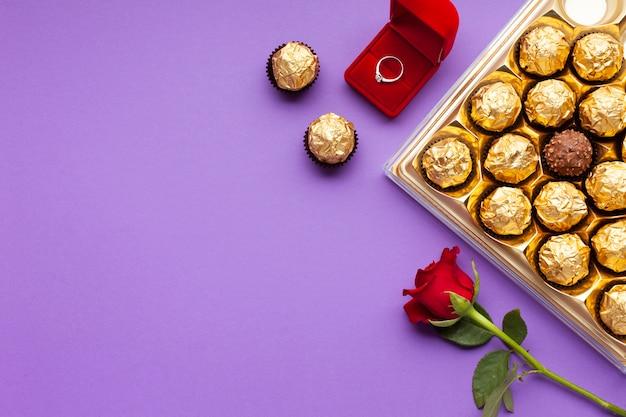 Dekoracja z widokiem z góry z pierścionkiem, różą i pudełkiem czekoladowym