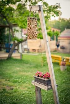 Dekoracja zewnętrzna - wiklinowa latarnia ogrodowa i doniczka na drewnianym stojaku.