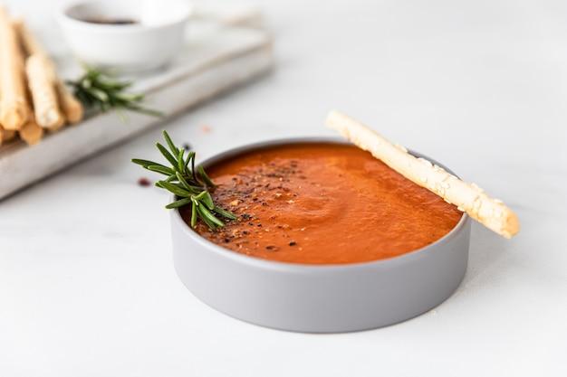 Dekoracja zupy pomidorowej z mielonym pieprzem, rozmarynem i paluszkami chlebowymi, jasna powierzchnia