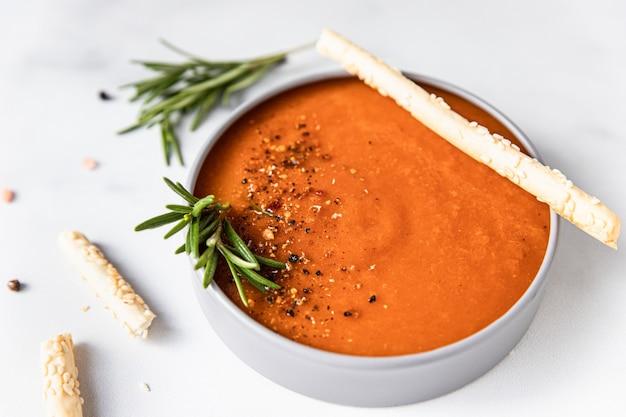 Dekoracja zupy pomidorowej z mielonym pieprzem, rozmarynem i paluszkami chlebowymi