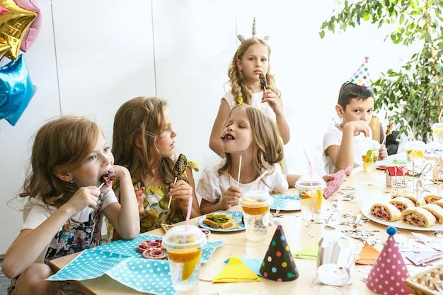 Dekoracje dla dzieci i urodzin. chłopcy i dziewczęta przy stole z jedzeniem, ciastami, napojami i gadżetami na przyjęcia.