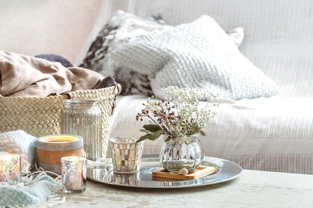 Dekoracje domu we wnętrzu. turkusowy koc i wiklinowy kosz z wazonem z kwiatami i świecami