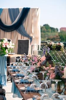 Dekoracje imprezowe na zewnątrz czas letni kwiaty świece niebieskie serwetki drewniane stoły