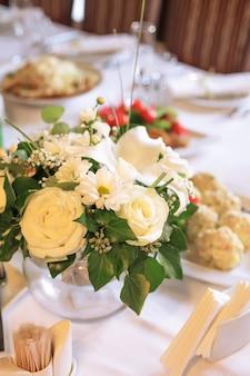 Dekoracje kwiatowe na stole bankietowym, przygotowane na imprezę okolicznościową lub wesele