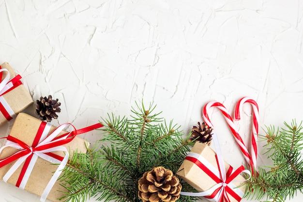 Dekoracje na boże narodzenie lub nowy rok pokrywają szyszki, gałęzie jodły, pudełka na prezenty i laski z cukierkami