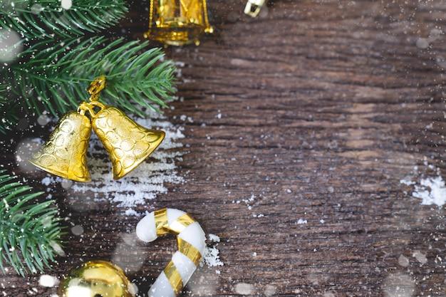 Dekoracje na boże narodzenie ze złotym dzwonkiem i ramką leafs na drewnianym stole.