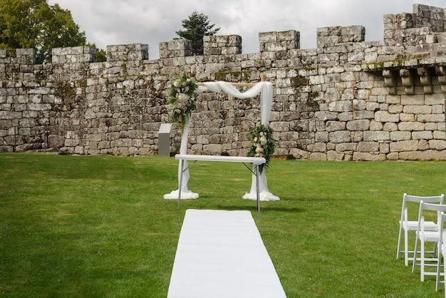 Dekoracje na ceremonię ślubną na zielonym trawniku starego zamku