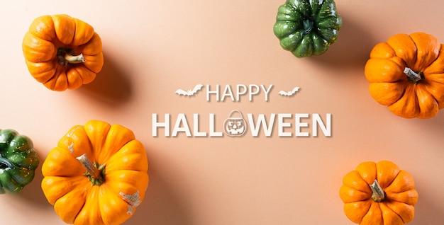 Dekoracje na halloween wykonane z dyni na pastelowym pomarańczowym tle