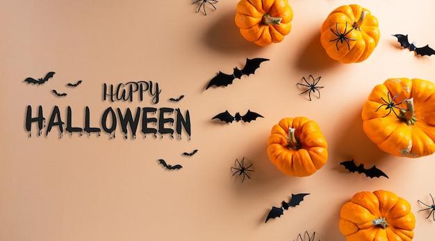 Dekoracje na halloween wykonane z dyni, papierowych nietoperzy i czarnego pająka
