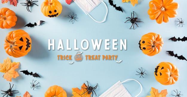 Dekoracje na halloween wykonane z papierowych nietoperzy dyni i chirurgicznej maski na pastelowym tle