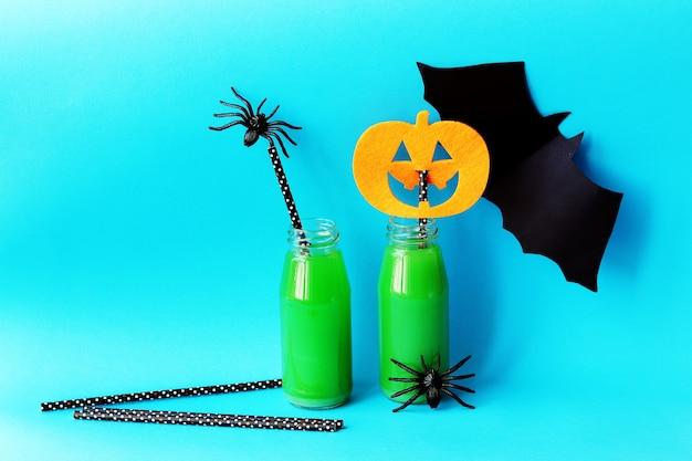 Dekoracje na halloween zielony koktajl ze słomką na jasnym niebieskim tle