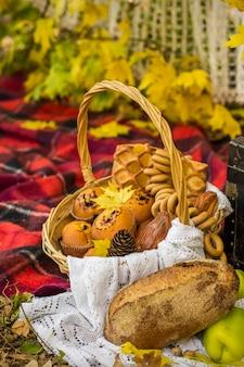 Dekoracje na jesienny piknik w lesie. retro zdjęcie w przyrodzie. jesienne ciepłe dni. babie lato. rustykalna jesień martwa natura. żniwa lub święto dziękczynienia. jesienny wystrój, impreza. ciasta w wiklinowym koszu