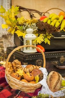 Dekoracje na jesienny piknik w lesie. retro zdjęcie w przyrodzie. jesienne ciepłe dni. babie lato. rustykalna jesień martwa natura. żniwa lub święto dziękczynienia. jesienny wystrój, impreza. latarnia, walizki vintage