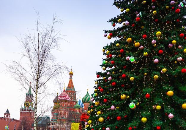 Dekoracje na nowy rok i święta. bombki choinkowe na gałęziach drzew w pobliżu katedry wasyla błogosławionego na placu czerwonym w moskwie
