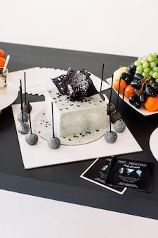 Dekoracje na przyjęcie urodzinowe. stylowy biało-czarny zdobiony tort urodzinowy i świeże owoce na czarnym stole. koncepcja przyjęcia urodzinowego