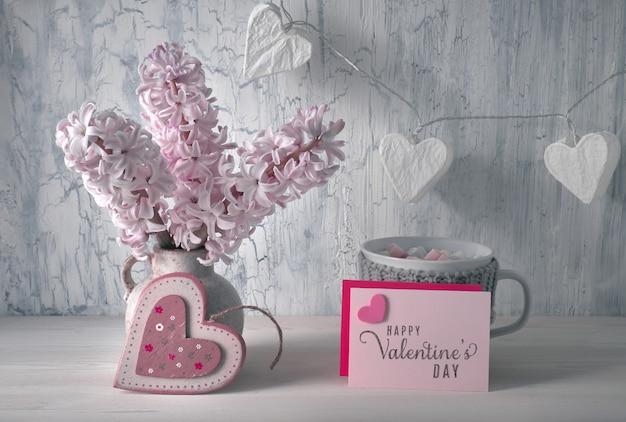 Dekoracje na walentynki, biały organizer na biurko z drewnianym kalendarzem, kubek gorącej czekolady i różowe kwiaty hiacyntu
