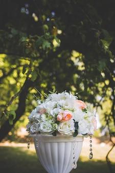 Dekoracje ślubne. kwiaty w białym wazonie.