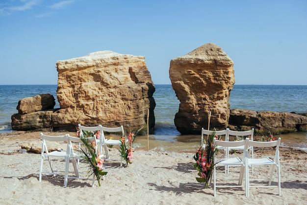 Dekoracje ślubne w stylu tropikalnym. konfiguracja ceremonii ślubnej na piaszczystej plaży.