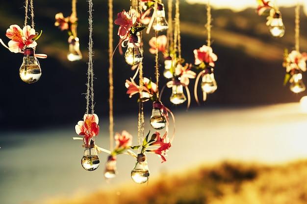 Dekoracje ślubne z lamp i kolorów zawieszone są na linie na brzegu rzeki podczas zachodu słońca