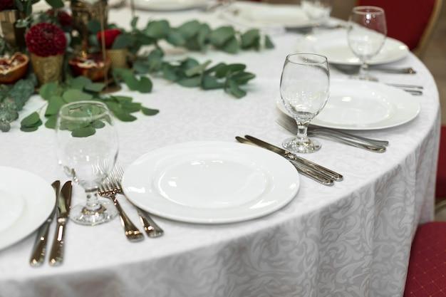 Dekoracje stołu weselnego zdobią świeże kwiaty w mosiężnej misce i złote świece w mosiężnych świecznikach.