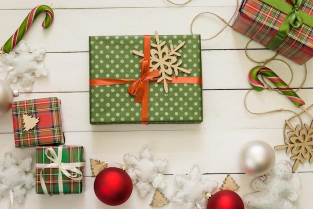Dekorację świąteczną, pudełka na prezenty, tło koncepcja ramki, widok z góry, na białej powierzchni stołu z drewna. ozdoby świąteczne i prezenty