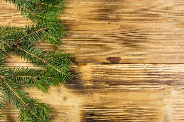 Dekorację świąteczną z gałęzi jodłowych na tle drewna. gałązki świerkowe na drewnianym stole. widok z góry, kopia miejsca